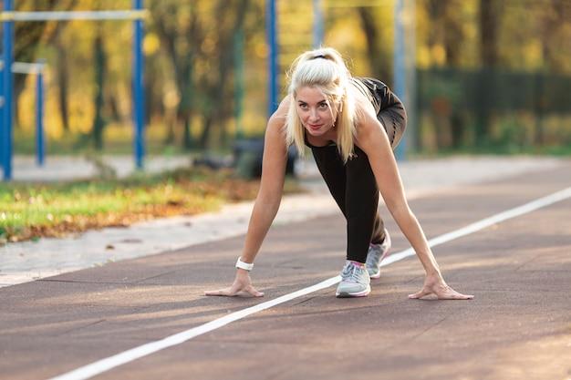 Schöne blonde frau, die sich vorbereitet zu laufen