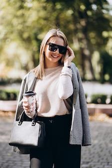 Schöne blonde frau, die sonnenbrille auf straße gehend trägt. stilvolle lächelnde geschäftsfrau mit kaffee in der dunklen freizeithose und im cremigen pullover. weiblicher geschäftsstil. hohe auflösung.