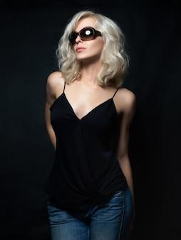 Schöne blonde frau, die sonnenbrille posiert. modellversuche. lustige mode