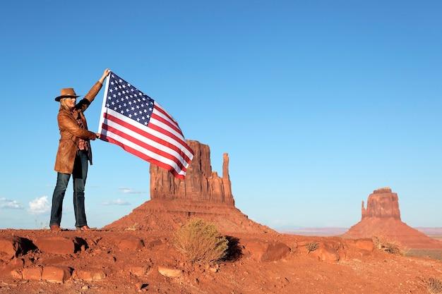Schöne blonde frau, die usa-flagge am monument valley hält