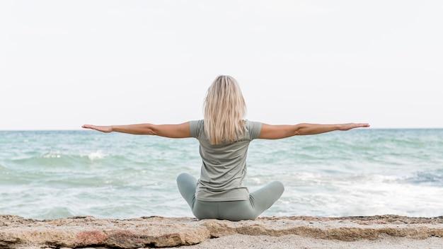Schöne blonde frau, die yoga am strand tut