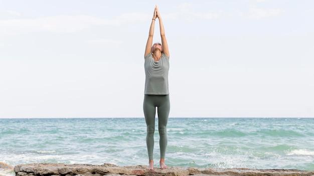 Schöne blonde frau, die yoga im freien praktiziert