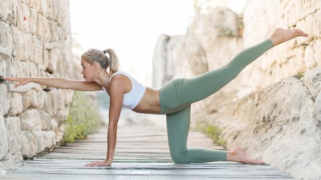 Schöne blonde frau, die yoga im freien tut