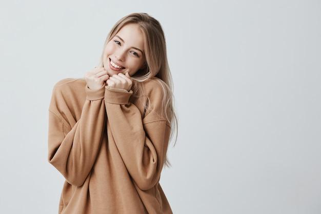 Schöne blonde frau drückt glückliche gefühle aus, in braunem pullover, hat breites angenehmes lächeln, froh, geschenk zu erhalten. das lächelnde überglückliche weibliche model genießt das leben isoliert