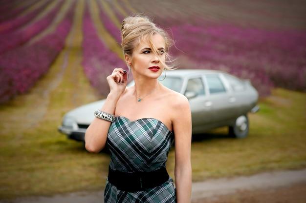 Schöne blonde frau, gekleidete französische art, die am retro-auto nahe lavendelfeld geht