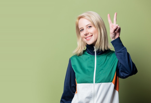 Schöne blonde frau im 90er jahre sportanzug zeigen ok geste