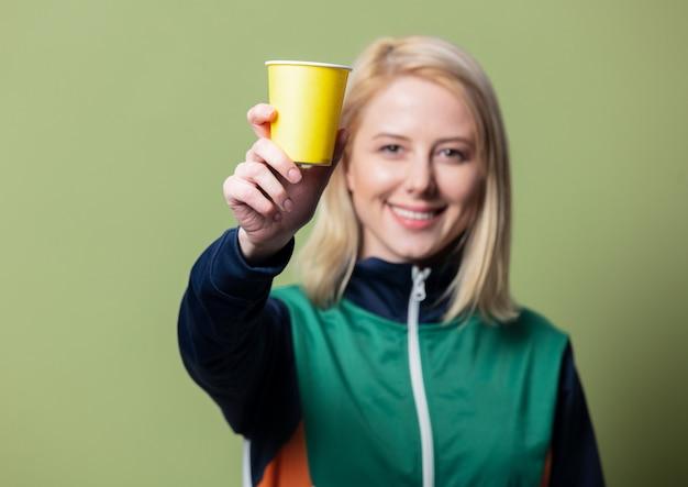Schöne blonde frau im 90er sportanzug mit pappbecher