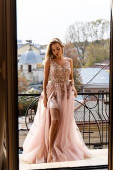 Schöne blonde frau im abendkleid, das auf dem balkon steht.