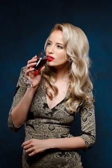 Schöne blonde frau im abendkleid, das wein auf party trinkt