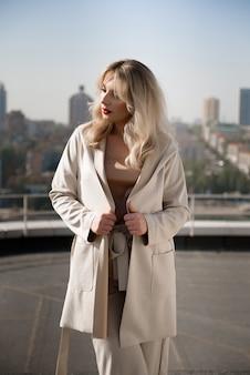 Schöne blonde frau im beige mantel, der auf dem dach des hauses steht.