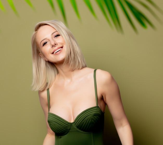 Schöne blonde frau im bikini nahe palmblättern