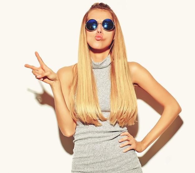 Schöne blonde frau im grauen sommer des zufälligen hippies kleidet ohne das make-up, das auf weiß lokalisiert wird, das ein entengesicht macht und friedenszeichen zeigt und ein entengesicht macht