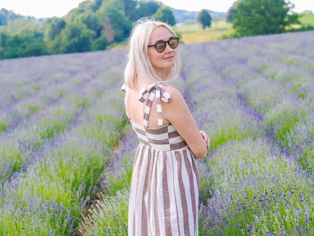 Schöne blonde frau im kleid sitzen zwischen lavendelfeldern in der provence. violette lavendelfelder, die im sommersonnenlicht blühen. meer der fliederblumen landschaft. bündel duftender blumen der französischen provence