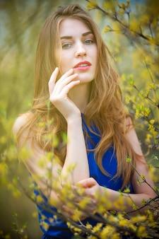 Schöne blonde frau im park an einem warmen frühlingstag