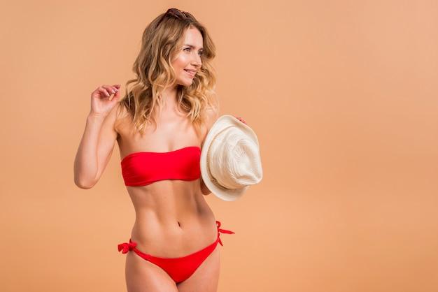 Schöne blonde frau im roten badeanzug, der hut hält