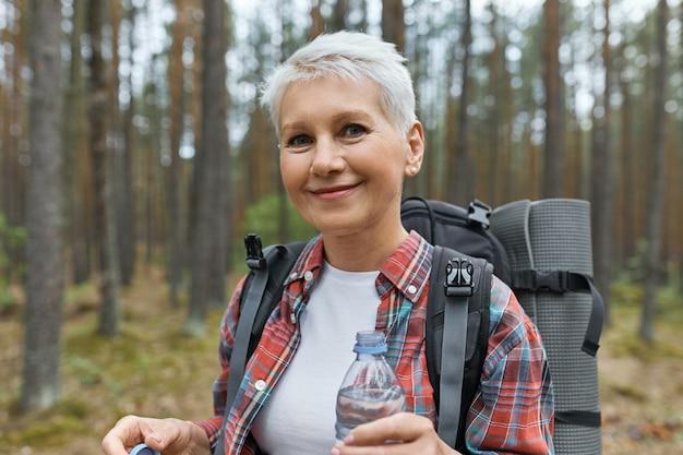 Schöne blonde frau im ruhestand, die urlaub im freien verbringt, im wald mit rucksack hinter ihrem rücken spazierend, plastikflasche wasser haltend