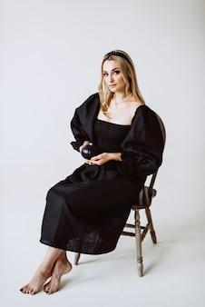 Schöne blonde frau im schwarzen leinenkleid mit einem kürbis in ihren händen. ethnische mode, natürlicher stoff. weicher selektiver fokus.