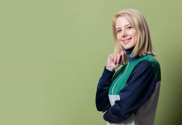 Schöne blonde frau im sportanzug der 90er jahre auf grünem hintergrund