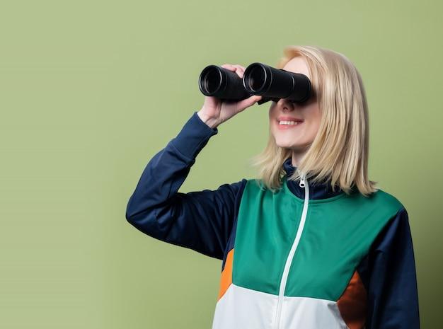 Schöne blonde frau im sportanzug der 90er jahre mit fernglas