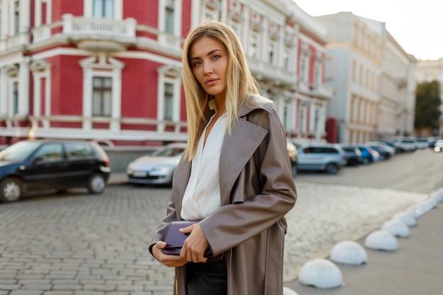 Schöne blonde frau im trendigen herbstoutfit, das in der stadt geht