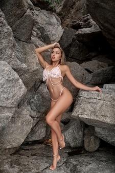 Schöne blonde frau in dem gestrickten weißen badeanzug, der nahe felsen am einsamen strand steht. boho-stil. perfekter schlanker körper. strandmode