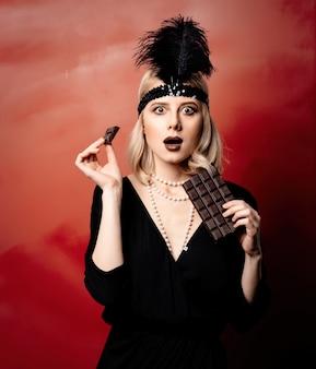 Schöne blonde frau in den zwanziger jahren kleidet mit schokoladenscheibe