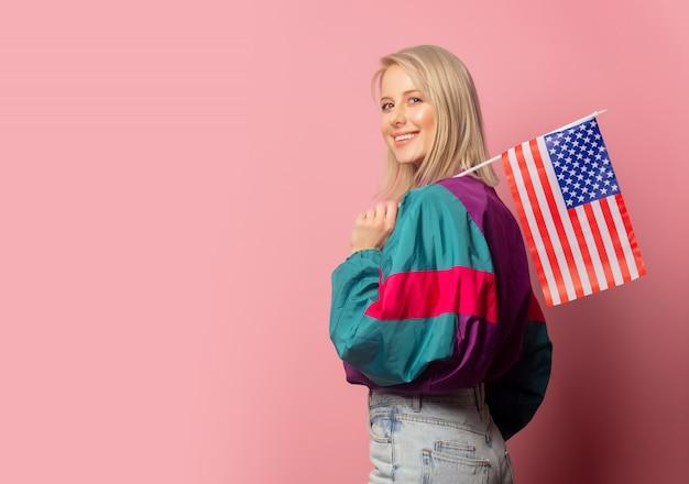 Schöne blonde frau in der kleidung der 90er jahre mit usa-markierungsfahne