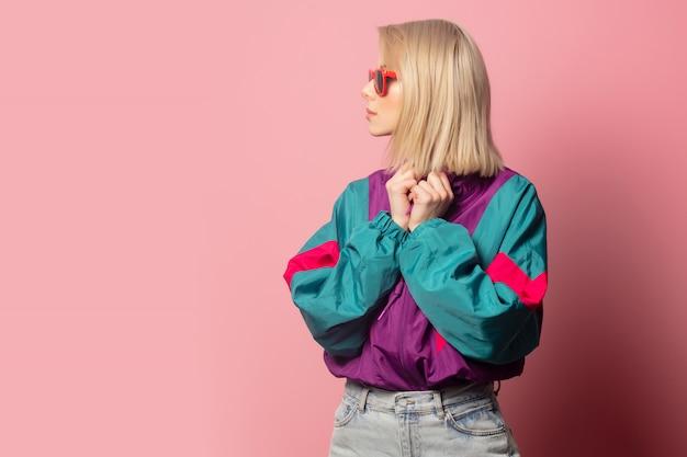 Schöne blonde frau in der sonnenbrille und in der kleidung der 90er jahre