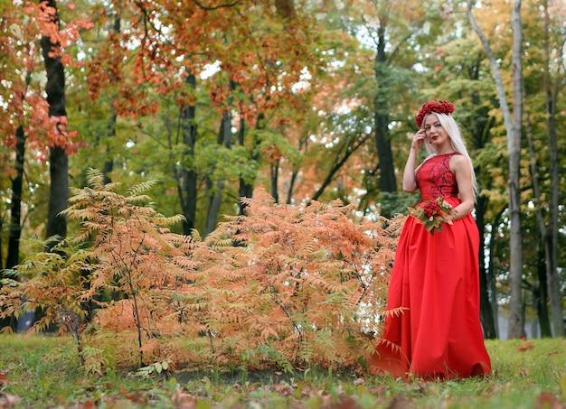 Schöne blonde frau in einem roten kleid, die in der gasse im herbstpark mit ebereschenblumenstrauß spaziert