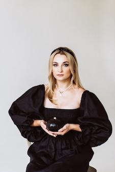 Schöne blonde frau in einem schwarzen leinenkleid mit einem kürbis in ihren händen. ethnische mode, natürlicher stoff. halloween party. weicher selektiver fokus.