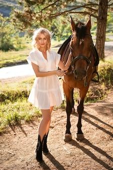 Schöne blonde frau in einem weißen kleid im wald mit einem pferd an einem sonnigen sommertag