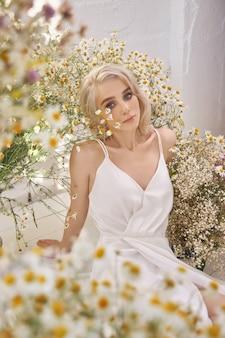 Schöne blonde frau in einem weißen kleid sitzt auf dem boden zwischen den kamillenblüten. porträt eines mädchens mit den wilden blumen des blumenstraußes