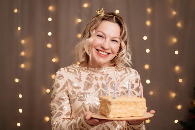 Schöne blonde frau in einer kleinen krone auf dem kopf mit einem geburtstagskuchen und kerzen. tradition, sich etwas zu wünschen und das feuer auszublasen. es ist eine party.