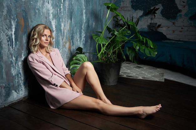 Schöne blonde frau in einer sexy rosa jacke. schönheitsporträt eines mädchens nahe der wand, saubere empfindliche haut von gesicht und körper