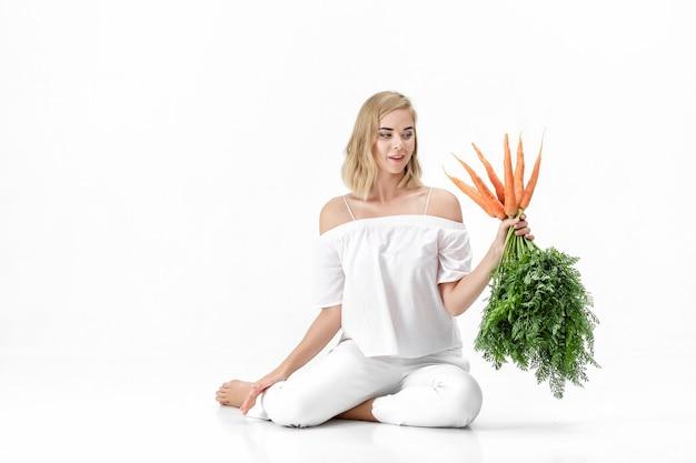 Schöne blonde frau in einer weißen bluse, die eine frische karotte mit grünen blättern auf einem weißen hintergrund hält. gesundheit und ernährung