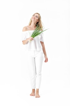 Schöne blonde frau in einer weißen bluse, die eine grüne zwiebel auf einem weißen hintergrund hält. gesundheit und vitamine