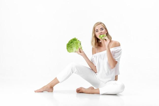Schöne blonde frau in einer weißen bluse, die einen frischen grünen salat auf einem weißen hintergrund isst. gesundheit und ernährung