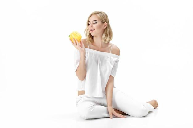 Schöne blonde frau in einer weißen bluse, die gelben paprika hält. gesunde ernährung und ernährung