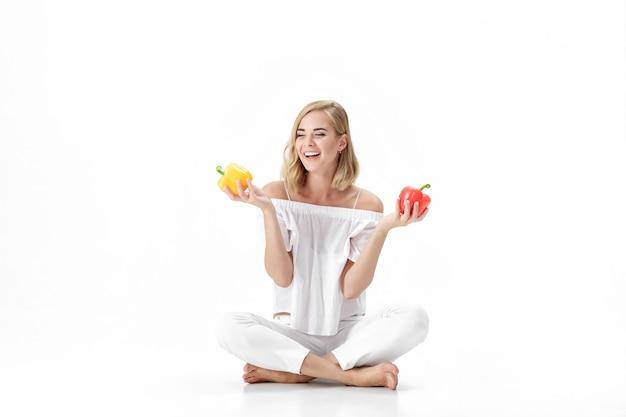 Schöne blonde frau in einer weißen bluse, die gelben und roten paprika hält. gesunde ernährung und ernährung
