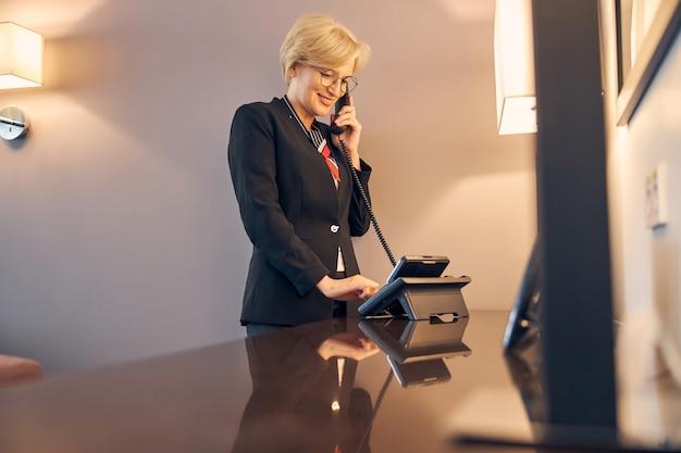 Schöne blonde frau in eleganter jacke, die am telefon spricht und lächelt