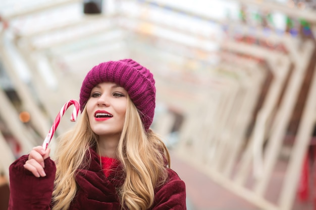 Schöne blonde frau in roter strickmütze posiert mit zuckerstange auf der straße