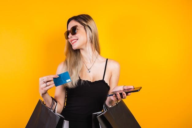 Schöne blonde frau in schwarz mit schwarzen einkaufstüten mit kreditkarte