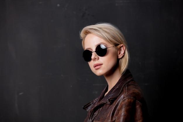 Schöne blonde frau in sonnenbrille und stiljacke