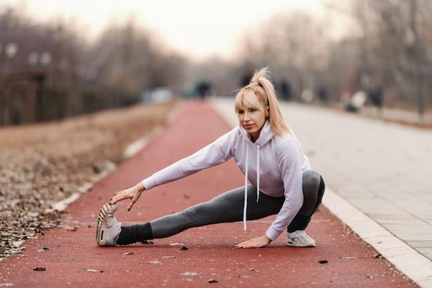 Schöne blonde frau in sportbekleidung, die beine streckt, bevor sie draußen läuft.