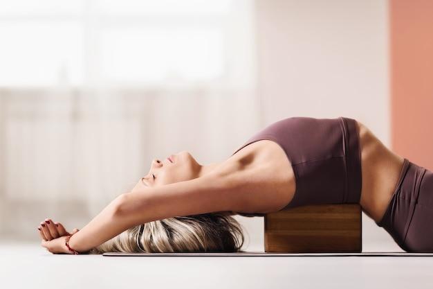 Schöne blonde frau in sportbekleidung liegt auf einem holzblock für yoga, um haltung zu verbessern