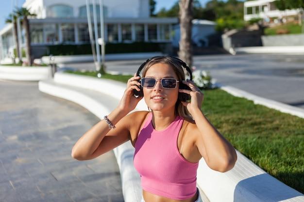 Schöne blonde frau in stilvoller kleidung und sonnenbrille hört musik mit kopfhörern im freien am sonnigen sommertag