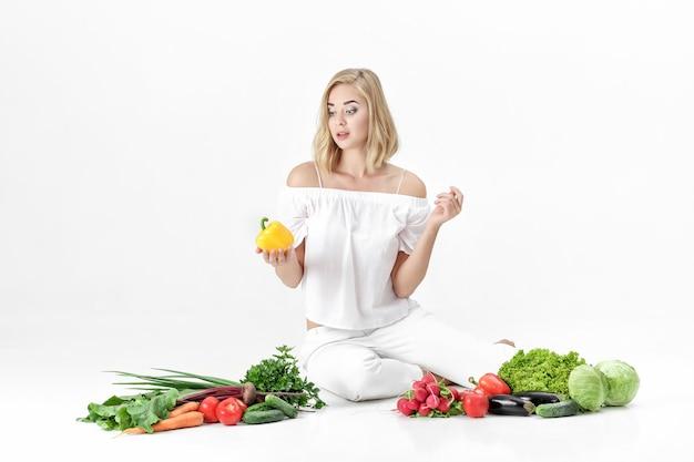 Schöne blonde frau in weißen kleidern und viel frischem gemüse auf einem weißen hintergrund. mädchen hält paprika