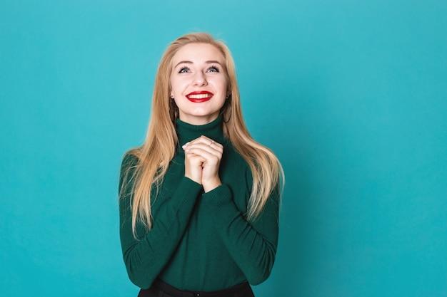 Schöne blonde frau ist für etwas dankbar, das auf einer tragenden strickjacke des blauen hintergrundes steht