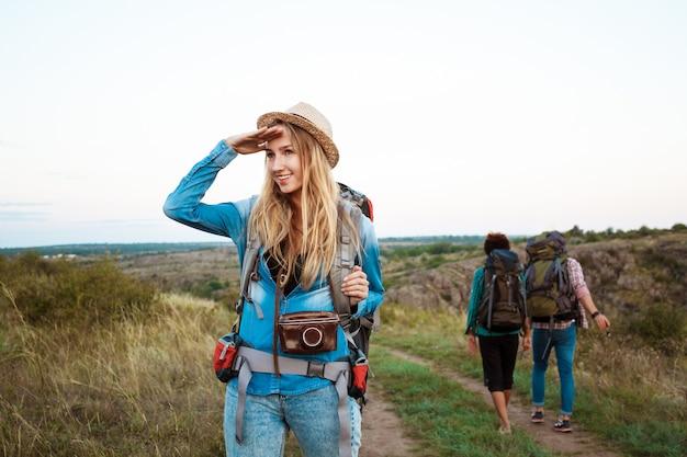 Schöne blonde frau lächelnd, blick in die ferne, freunde touristen hintergrund