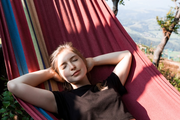 Schöne blonde frau lächelnd, ruhend in der hängematte in den karpaten